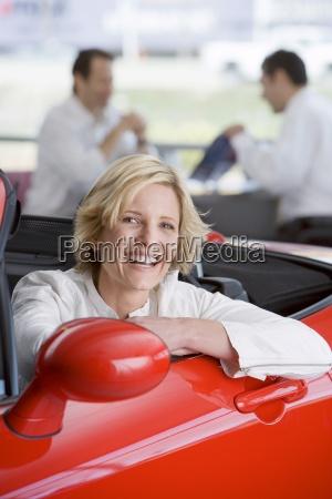 saelger med kunden i bil showroom