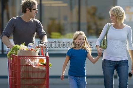 familie verlassen supermarkt vater schieben einkaufswagen