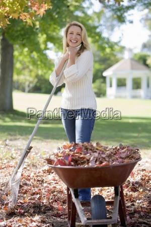 kvinde indsamling efterarsblade i haven staende