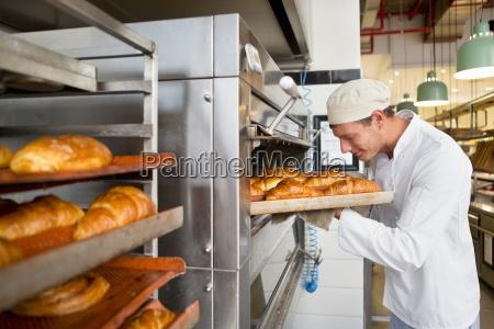 smilende bager kontrol bakke med brod