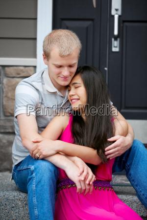 unge glade forskellige par sidder sammen