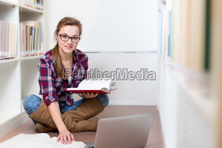 pretty kvindelig universitetsstuderende i et bibliotek