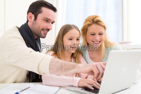 lykkelig familie foran en baerbar computer