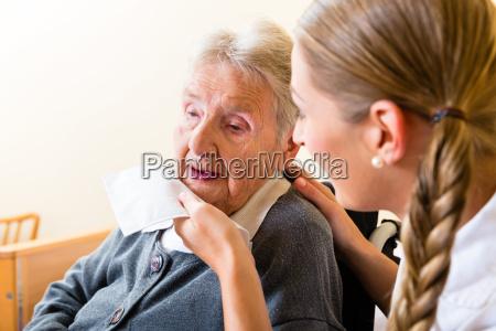 altenpflegerin klude gammel kvindes mund fra
