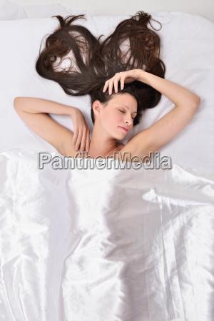 smuk kvinde pa sengen under hvidt