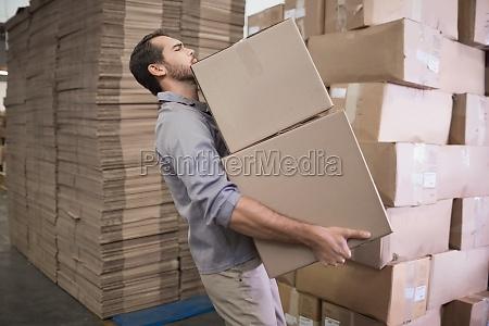 worker transporterer kasser i lageret