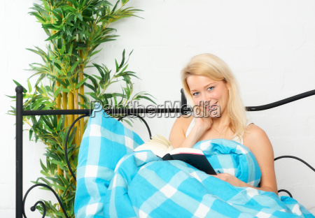 young woman sitting in bed reading