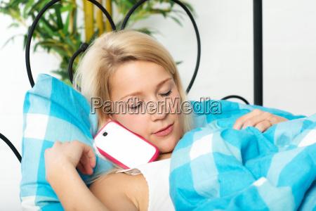 blond kvinde med mobiltelefon i sengen