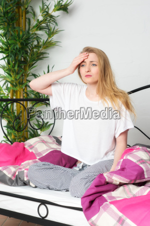 scattered young woman sitting in bed