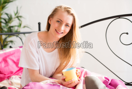 blonde young woman enjoying a cup