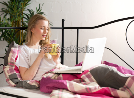 young woman with laptop in bed