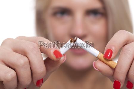 unge blonde kvinde bryder en cigaret