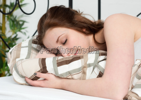 young woman sleeping relaxing in bed
