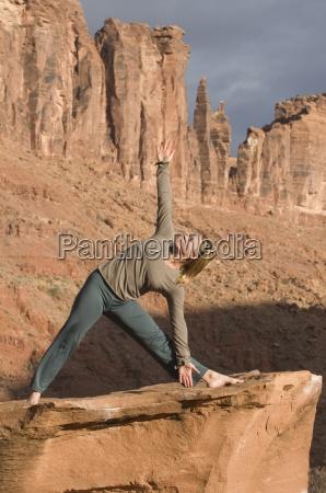 kvinde i yoga pose pa sandsten