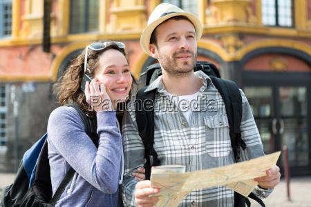 par unge attraktive turister ser kort