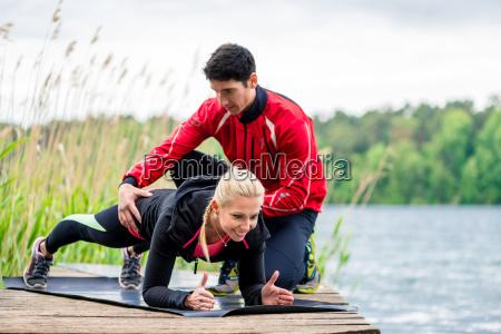 kvinde med person traener gor fitness