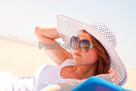 kvinde i en hat pa stranden