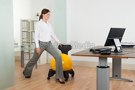 forretningskvinde motion med pilates ball pa