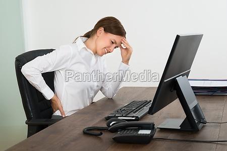 forretningskvinde som lider af rygsmerter og
