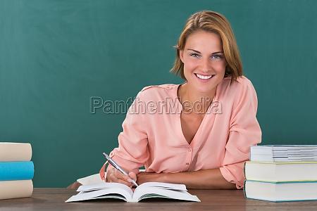 kvinde laerer studerende ved skrivebord