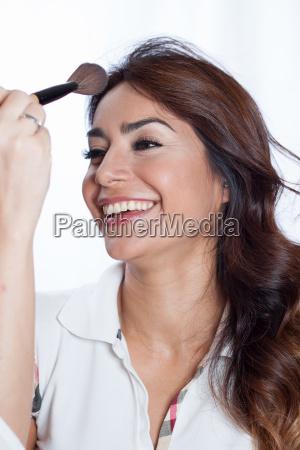 kvinde smilende med en makeup borste