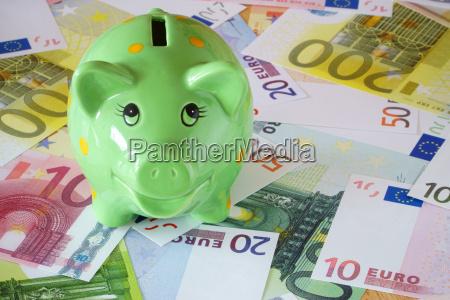 gron piggy bank og eurosedler pa