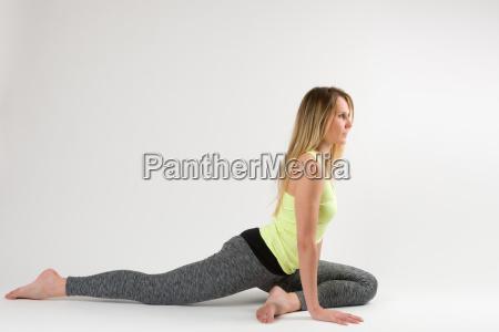 blond kvinde laver yoga og straekovelser