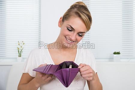 kvinde kigger pa penge i pung
