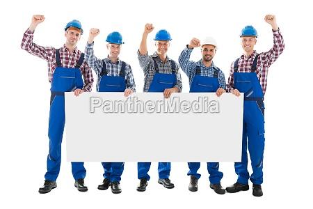 mandlige snedkerer med arms raised holding