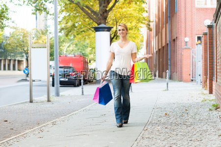 happy woman carrying shopping bags on