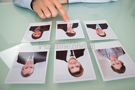 biznesmen recznie wybierajac fotografie kandydata