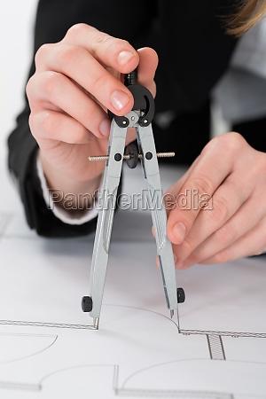 kvindelig arkitekt haender bedrift kompas pa