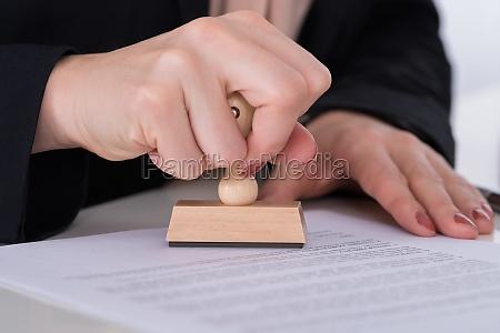 forretningsmand der bruger stamper pa dokument