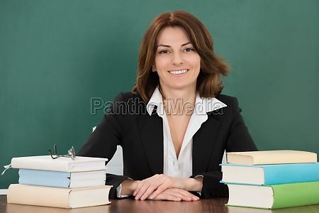 kvindelig laerer sidder ved klassevaerelset desk