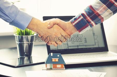 ejendomsmaeglerbureau rystende haender med kunden efter
