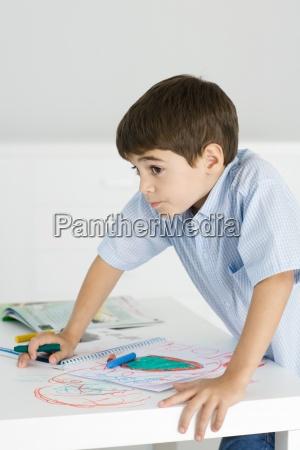 boy haelder pa bordet holde farvekridt