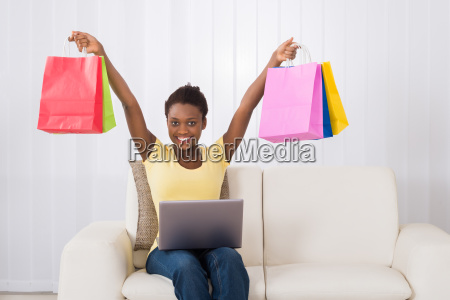 woman holding multi colored shopping bags