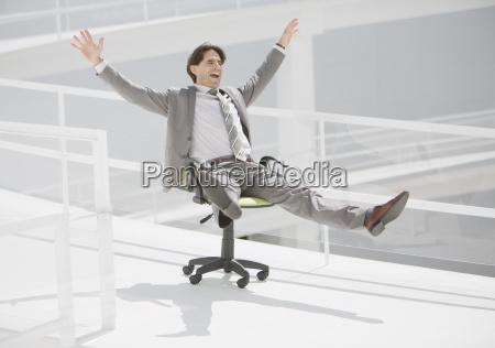 carefree businessman sliding down walkway on
