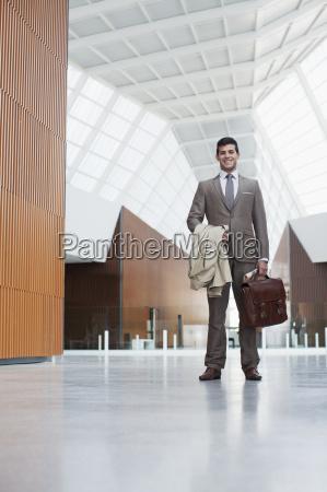 portrait of smiling businessman holding coat