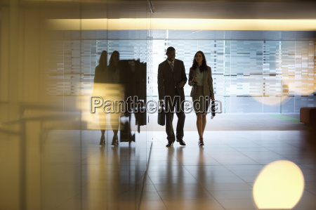 businessman and businesswoman walking in lobby