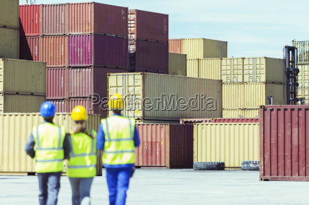 workers and businessman walking near cargo