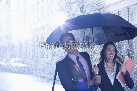 happy businessman and businesswoman walking under
