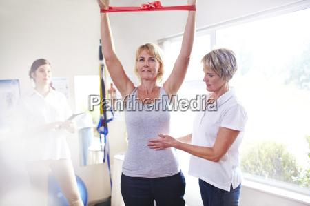 fysioterapeut vejlede kvinde traekke modstand band