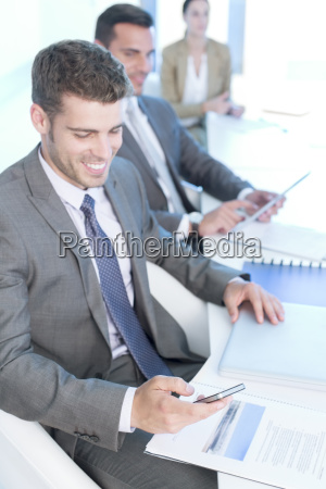 businessman texting with cell phone in