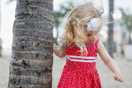maedchen mit haarband am palmenstamm