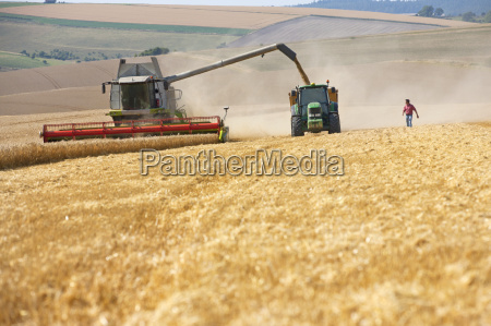 farmer nearing combine harvester filling tractor