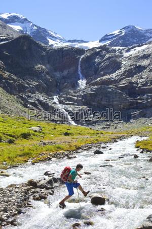 en mandlig vandrer hoppe fra sten