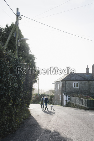 two women walking along a village