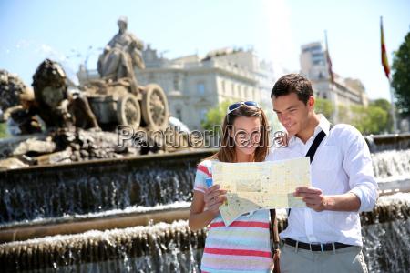 kilka turystow czytajac mape w plaza