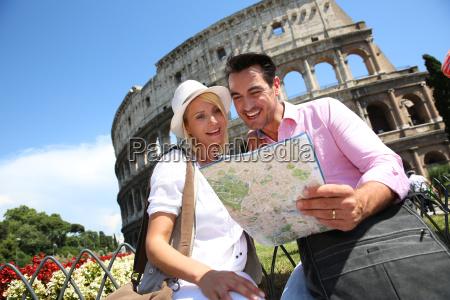 turister der laeser kort foran colosseum